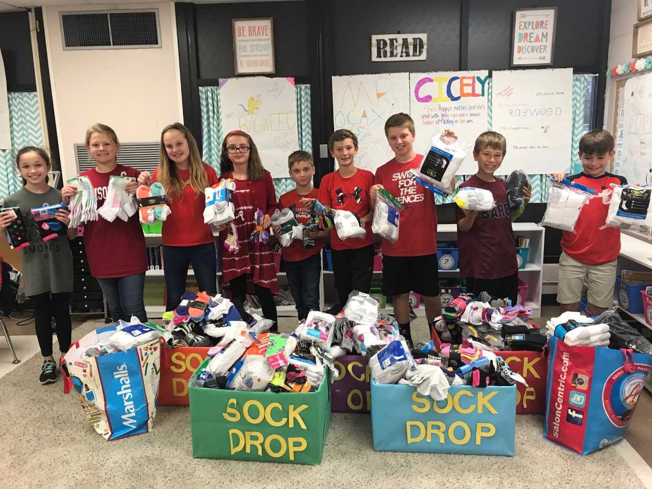 kids with boxes of socks that were collected for a service project