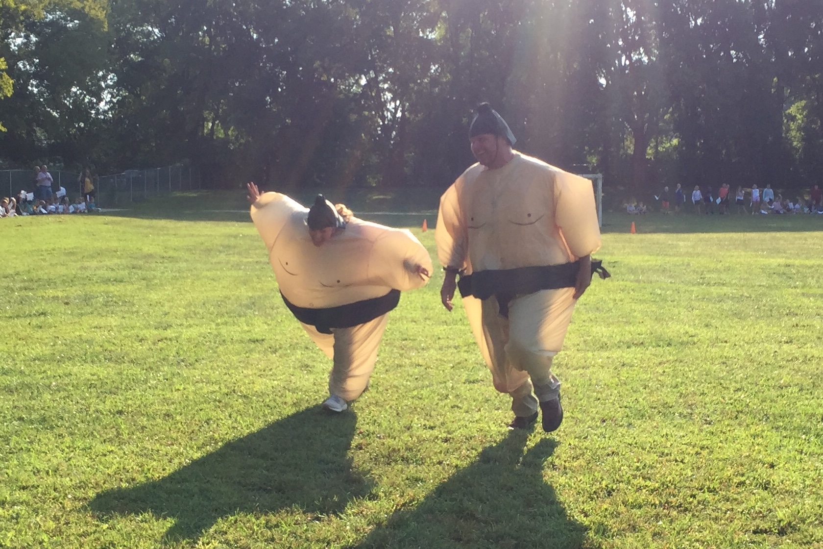 Mr. Taylor and Mrs. Holleman in Sumo suits racing down the soccer field