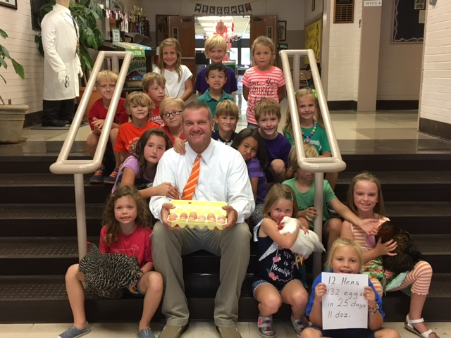 Principal sitting with first grade class holding eggs